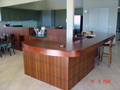 Curved solid Jarrah benchtop with display niches in servery panel in background